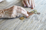 Hand of senior woman counting coins, close-up - RBF06990