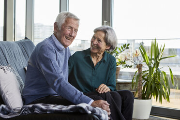 Laughing senior couple sitting together on couch - RBF06993