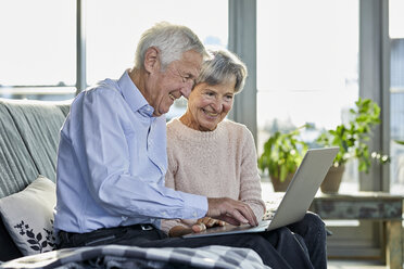 Senior couple sitting together on couch using laptop - RBF07002