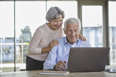 Portrait of smiling senior couple using laptop - RBF07005