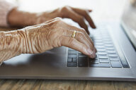 Hand of senior woman typing on keyboard of laptop, close-up - RBF07008