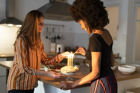 Friends preparing birtday cake with burning candles as a surprise - ERRF00591