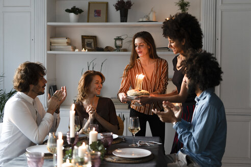 Friends surprising young woman with a birthday cake with burning candles - ERRF00594