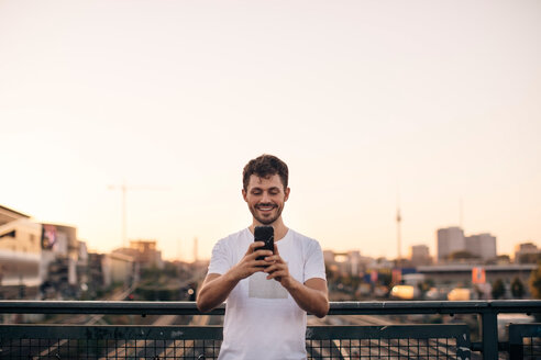 Smiling young man using mobile phone while standing on bridge against clear sky during sunset - MASF10321