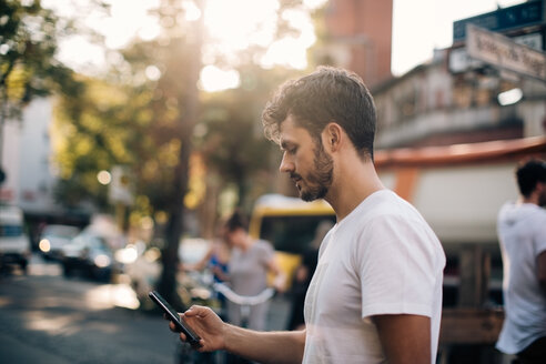 Side view of young man using mobile phone while standing on street in city - MASF10366