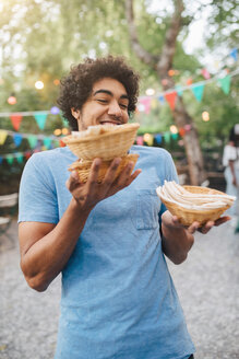 Smiling young man carrying food in bowls during dinner party in backyard - MASF10417
