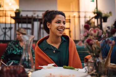 Smiling young woman looking away while sitting at table during dinner party - MASF10441