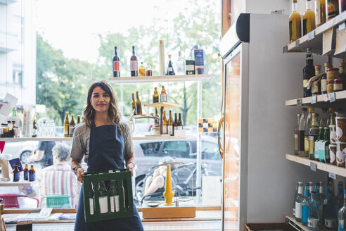 Portrait of confident female employee carrying bottles in crate at deli - MASF10561