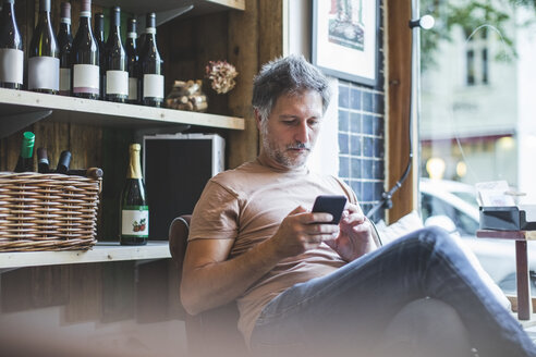 Mature owner using smart phone while sitting on chair in deli - MASF10585