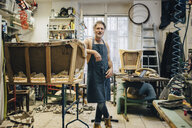 Portrait of mature male craftsperson standing by incomplete sofa in upholstery workshop - MASF10600