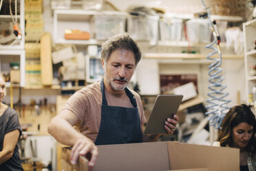 Craftsperson opening cardboard box in upholstery workshop - MASF10633