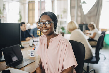 Portrait of smiling young businesswoman sitting at desk in creative office - MASF10663
