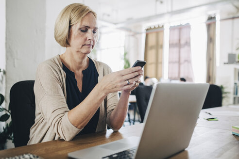 Mature businesswoman using mobile phone at desk in creative office - MASF10669