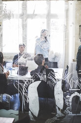 Business people in board room seen through patterned glass at creative office - MASF10735
