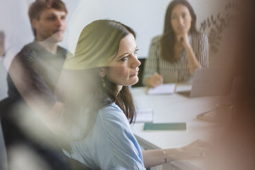 Businesswoman with colleagues listening while sitting at conference table during meeting in office - MASF10741