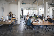 Multi-ethnic business people working at desks in office - MASF10756