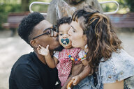 Mother and father kissing daughter sucking pacifier at playground - MASF10774