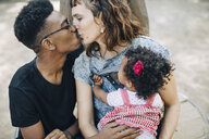 Baby girl looking at mother and father kissing in playground - MASF10777