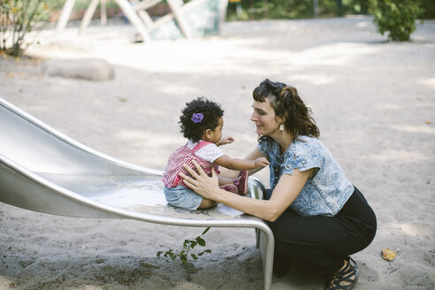 Side view of mother supporting daughter sitting on slide at playground - MASF10783
