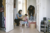 Daughter looking at mother and father packing luggage at home - MASF10789