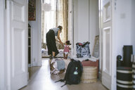 Mother assisting daughter in walking seen through doorway at home - MASF10795
