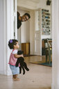 Happy father peeking at daughter holding stuffed toy in house - MASF10813