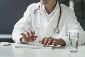 Close-up of doctor in medical practice typing on keyboard at desk - JOSF02774