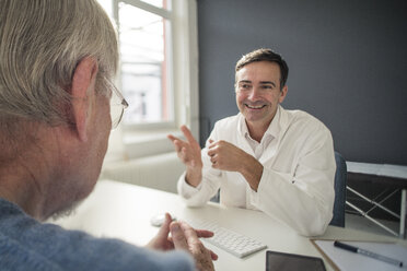 Smiling doctor talking to patient in medical practice - JOSF02777