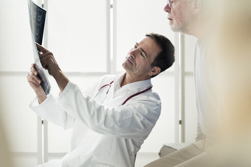 Doctor discussing MRT image with patient in medical practice - JOSF02783