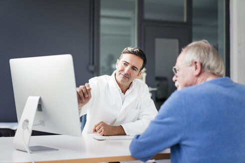 Doctor sharing computer screen with patient in medical practice - JOSF02801