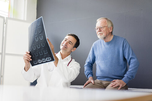 Smiling doctor discussing MRT image with patient in medical practice - JOSF02813
