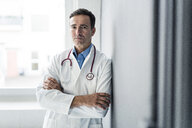 Portrait of serious doctor leaning against a wall - JOSF02816