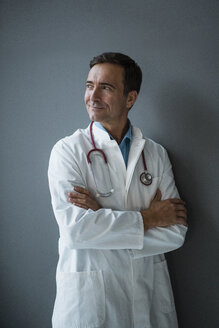 Smiling doctor standing at a grey wall looking sideways - JOSF02819