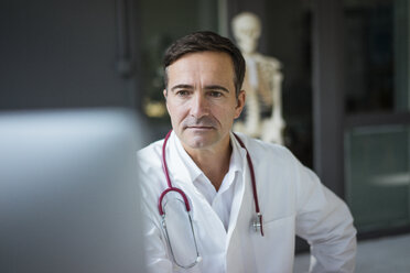 Doctor in medical practice looking at computer with skeleton in background - JOSF02831