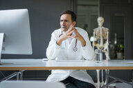 Serious doctor sitting at desk in medical practice with skeleton in background - JOSF02834