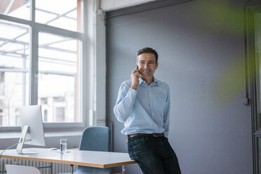 Smiling businessman on cell phone in the office - JOSF02837