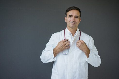 Portrait of confident doctor standing at a grey wall - JOSF02840
