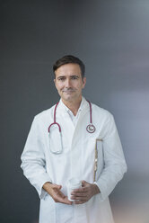 Portrait of confident doctor holding cup at a grey wall - JOSF02843