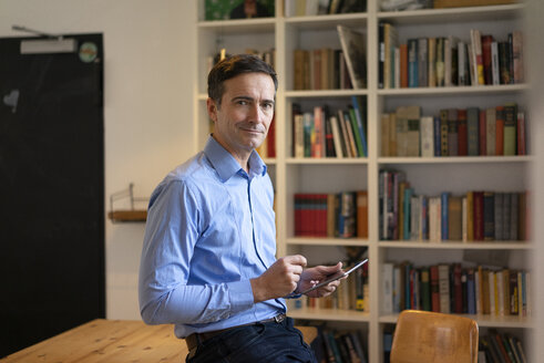 Portrait of confident businessman with tablet leaning at table with bookshelf in background - JOSF02846