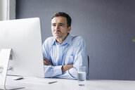 Serious businessman sitting at desk in office looking at computer screen - JOSF02861