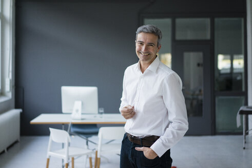 Portrait of smiling businessman in the office - JOSF02870