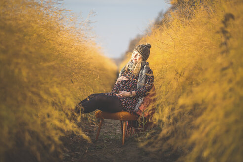 Pregnant woman sitting on chair in asparagus field in autumn - ASCF00916