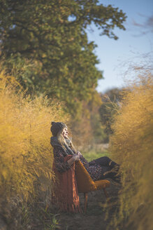 Pregnant woman sitting on chair in asparagus field in autumn - ASCF00919