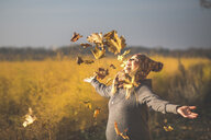 Happy pregnant woman playing with autumn leaves in nature - ASCF00925
