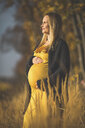 Smiling pregnant woman standing in nature in autumn - ASCF00928