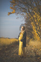 Smiling pregnant woman standing on forest path next to asparagus field in autumn - ASCF00937