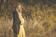 Pregnant woman standing on forest path in autumn - ASCF00940