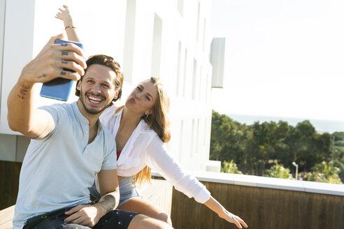 Couple on rooftop terrace, taking selfies - VABF02114