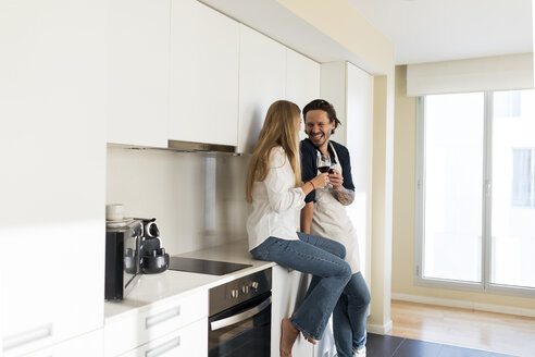 Affectionate couple drinking redwine in the kitchen - VABF02132