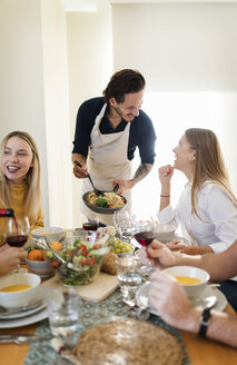 Friends having lunch together, host serving pasta - VABF02138